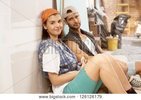 Young couple sitting on floor exhausted after daily work on home renovation.