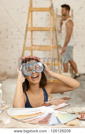 Young woman laughing in protective eyewear at home renovation.