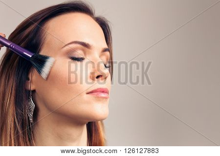 Makeup artist applies skintone on client face. Beautiful woman with eyes closed Perfect makeup. Skincare foundation. The process of working professional makeup.