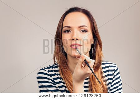 Beautiful girl gets lip gloss itself in the beauty salon. Portrait of beautiful young woman is looking at the camera like in the mirror.