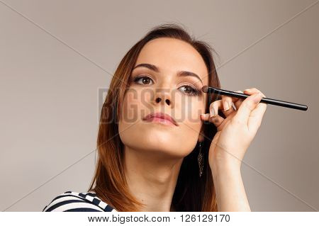 Beautiful woman applying colorful eye makeup in beauty salon. Extension eyelashes. Spa salon. Perfect face makeup. The process of working professional makeup.