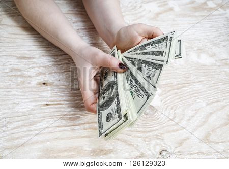 Cash in hands. Pile of one hundred dollar bills. Stack of dollars in hands. Woman counting money. Dollars in hands. Fake money in hands.