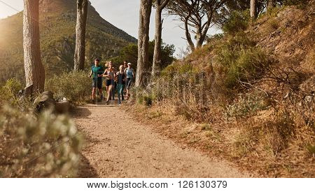 Group of athletes running together through trails on the hillside. Young people trail running on a mountain path outdoors.