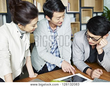 young asian businesspeople working together in office using tablet computer.