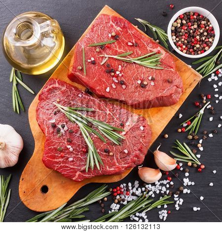 Raw beef steak with spices and ingredients for cooking on cutting borard and  slate background. Top view.