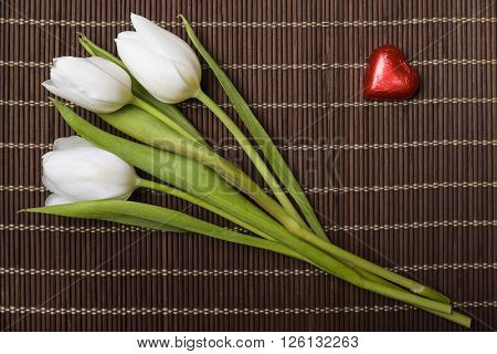 three white tulips and red chocolate heart on  wooden placemat