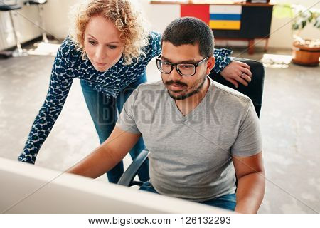 Portrait of two young graphic designers working on computer in office. Male and woman designers looking at computer monitor.