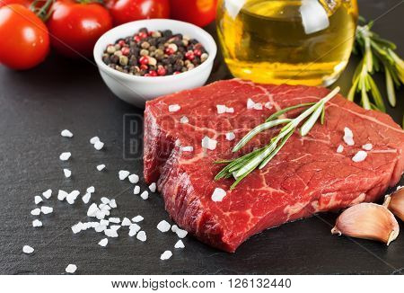 Raw steak with rosemary, salt and pepper on slate plate.