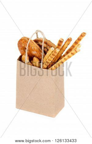 Snack bag hold in hand isolated on white. Delivery and sale of food. Cookie bread and cracker in supermarket package ready for logo design presentation.
