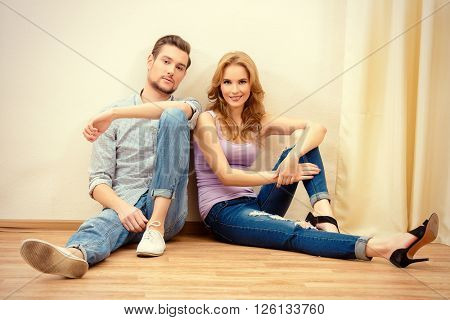 Happy couple sitting together on a floor at home. Moving to a new home. Apartment repair.