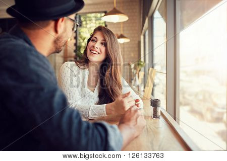 Smiling young woman sitting in a cafe and talking to her boyfriend. Young couple spending time at coffee shop.