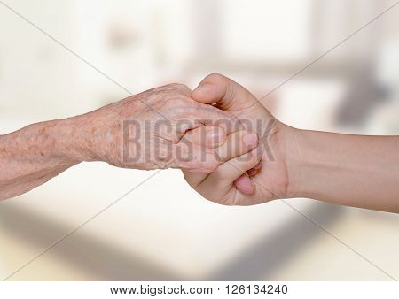 Young woman's hand holding old woman's hand in bedroom
