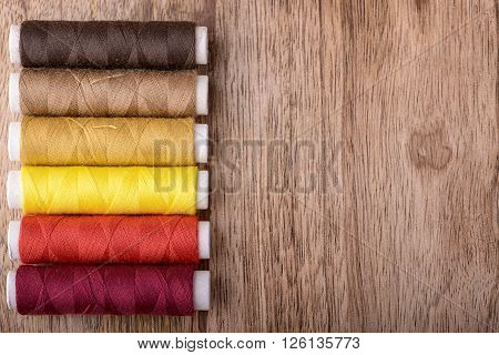 cotton sewing from red to brown on wood