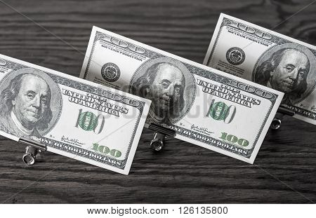 Hundred dollar bills in paper clips standing on a dark wooden background. Money in the paper clips. Fake money.