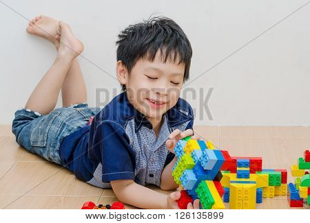 Young asian boy plying block on the floor