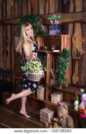 Beautiful young smiling woman with long blond hair,  wearing casual dress standing near vintage wooden shelf with books and bouquets in glass vases, holding wicker basket with artificial flowers
