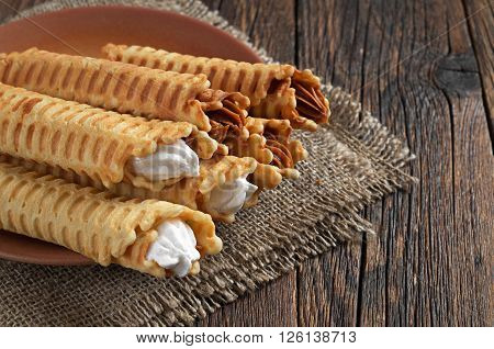 Waffle tubules with creamy in plate on dark wooden table