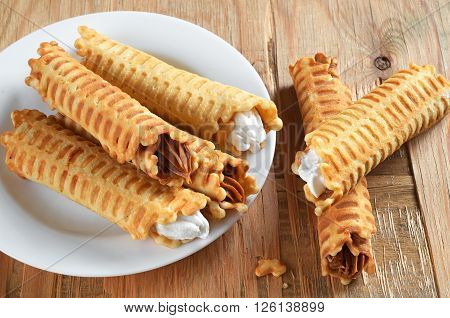 Waffle tubules with sweet creamy on rustic wooden table