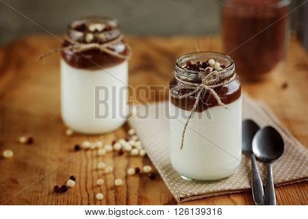 Yoghurtr with chocolate and brown-white chocolate drops with napkin on wooden background