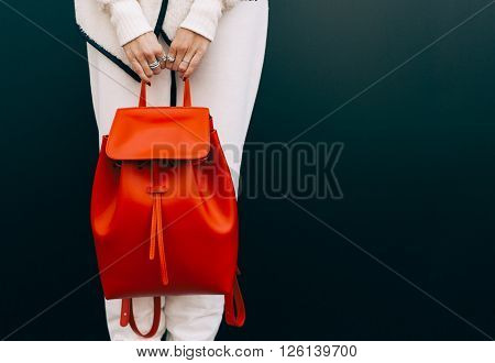 Fashionable beautiful big red backpack on the arm of the girl in a fashionable white sports suit, posing near the wall on a warm summer night. Warm color