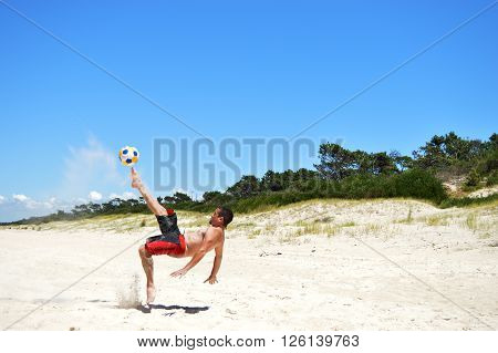 Uruguay , January 2016. Man plays ball on the beach. He performs tricks with the ball for fun. He lifts the sand with his kick and then falls, with the summer heat . This happened on a beach in Uruguay on the Rio de la Plata , in the summer of 2016.