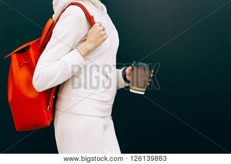 Fashionable beautiful big red backpack on the arm of the girl in a fashionable white sports suit, posing near the wall on a warm summer night. Cup of coffee in hand. Warm color