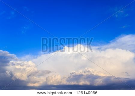 Blue sky background with white and dark rain clouds