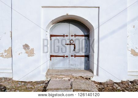 Old grey metal door with rusty metal door henges and handles in the medieval Slavic church. Closeup architectural view.
