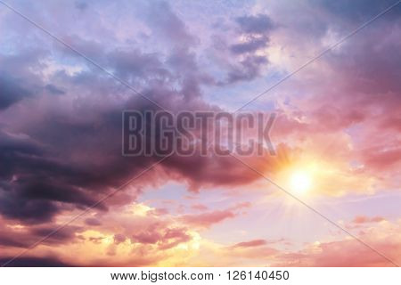 Colorful picturesque sky background with sun and huge dark rain clouds.