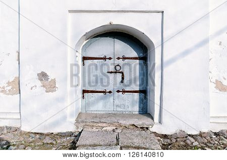 Aged steel door with rusty door henges and handles in the ancient Slavic church. Architectural background in natural tones.