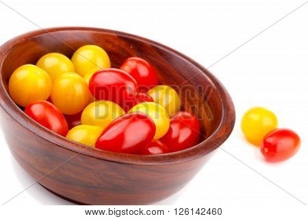 Yellow and red tomato cherry in wooden bawl isolated on white