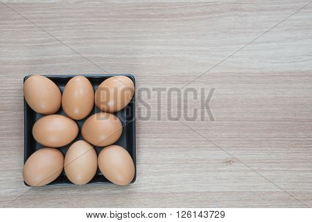 Eight eggs in black square plate on wooden surface with space for text