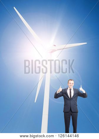 A wind turbine on a asunny day and a man