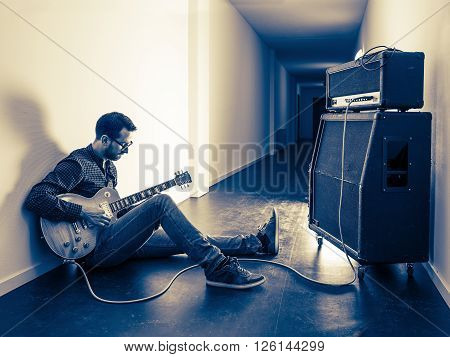 Photo of a man sitting playing his electric guitar in front of a large amplifier in a hallway. Filtered for retro vintage feel.
