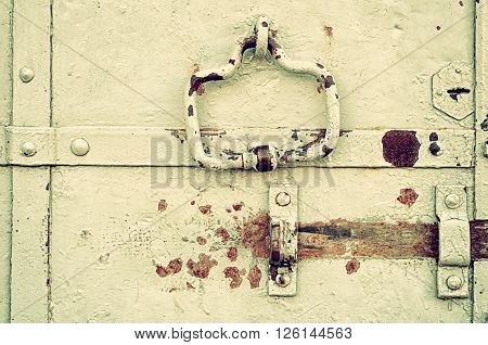 Aged steel door with peeling paint and rusty architectural details - rivets door handle and empty lanch. Textured architectural background in retro tones.