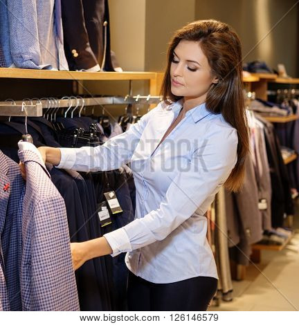 Beautiful young saleswoman helps the customer to choose a jacket in suit shop.