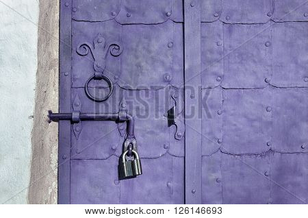 Vintage iron light violet door with plates rivets and old door handle formed as stylized lily. Aged architectural textured background