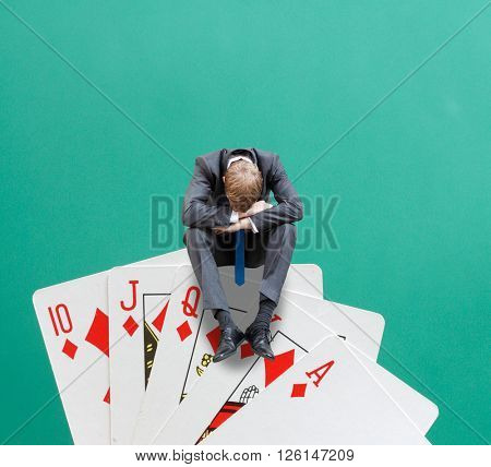 A gambler sitting on cards