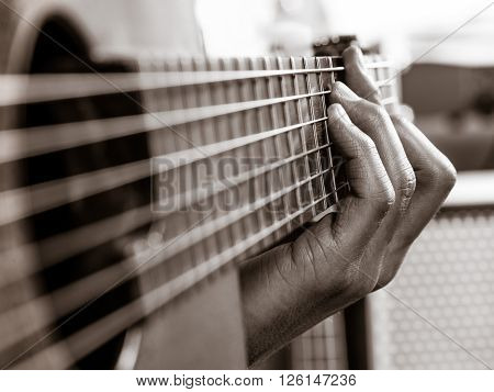 Closeup photo of a man playing his acoustic guitar. Focus on the fingers.