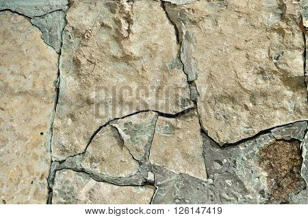 Rough background - surface of old cracked stone with deep fissures