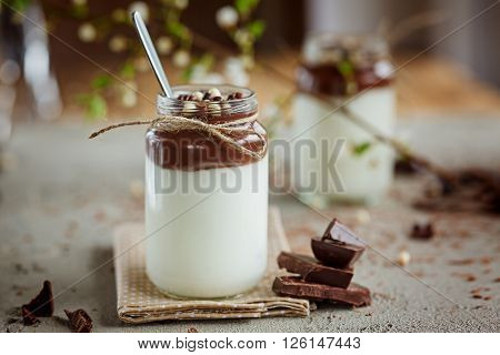 Homemade yogurt with chocolate mousse and  chocolate candy and spoon