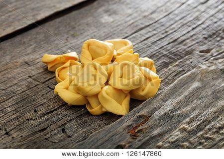 Uncooked tortellini set on wooden surface