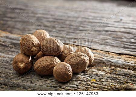 Dried nutmeg seeds set on old wooden surface
