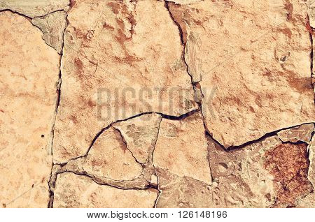 Closeup of old rough broken stone with deep crannies - stone textured background in warm antique vintage tones
