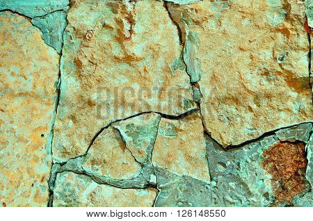 Old broken pale orange stone with deep green cracks. Stone rough background