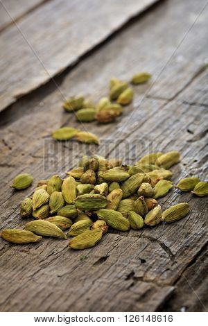 Dried cardamom pile set on old wooden surface
