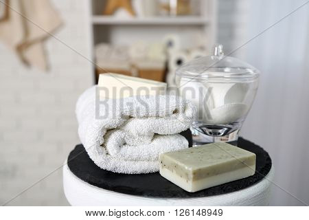 Bathroom set with towels, sponges and soap on stool in light interior