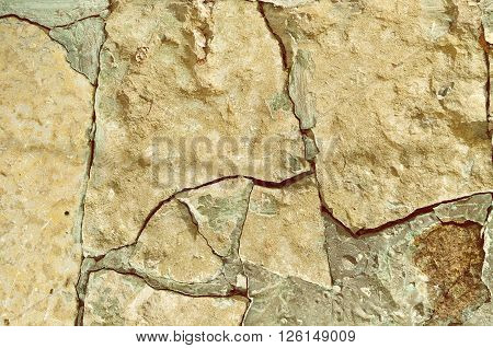 Stone retro tones background - old rough broken pale beige stone with deep fissures