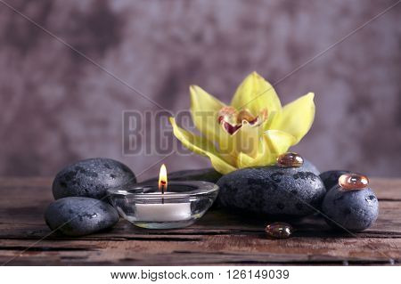 Spa still life with stones, flower and candlelight on blurred pastel background