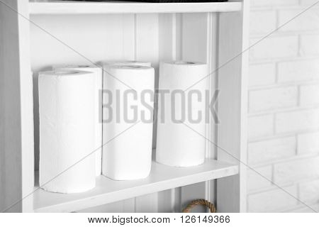 Bathroom set with paper towels on a shelf in light interior